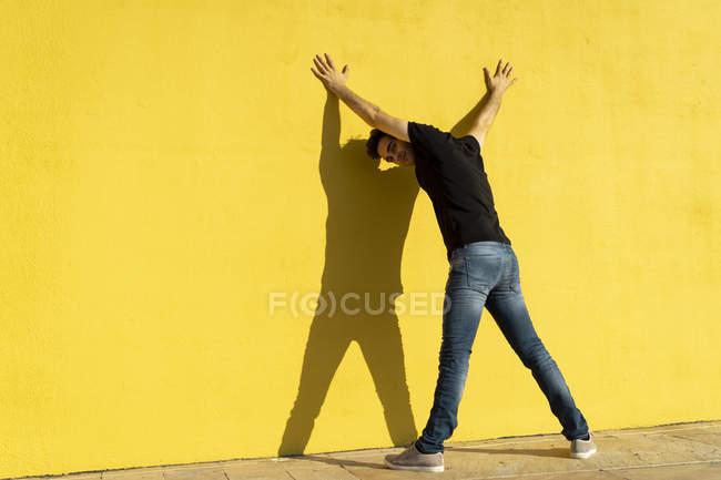 Homme debout avec les mains sur le mur jaune, vue arrière — Photo de stock
