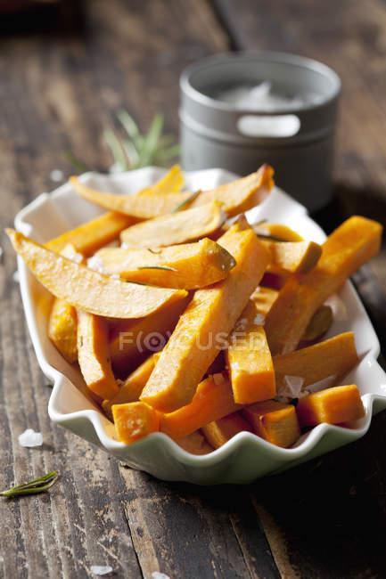 Картофель фри с романом и солью в фарфоровой чаше — стоковое фото