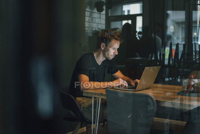 Mann sitzt im Büro und arbeitet spät in seinem Start-up-Unternehmen — Stockfoto