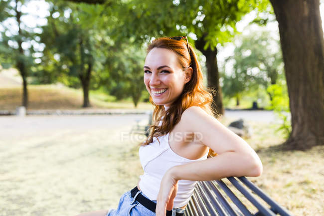 Portrait of laughing redheaded woman sitting on bench in park — Stock Photo