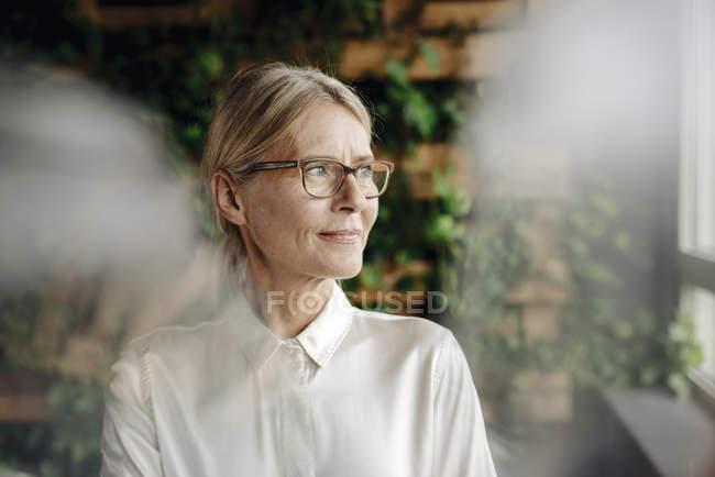 Imprenditrice in ufficio verde che guarda fuori dalla finestra — Foto stock