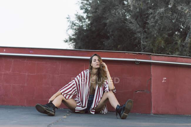 Жінка носить нестебнутій смугастій сорочці сидячи на землі — стокове фото