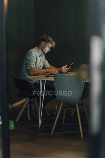 Homme fatigué s'asseyant dans le bureau, travaillant tard dans la compagnie de start-up — Photo de stock