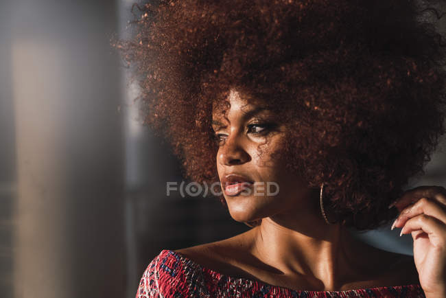 Portrait of sensual woman with dyed ringlets on blurred background — Stock Photo