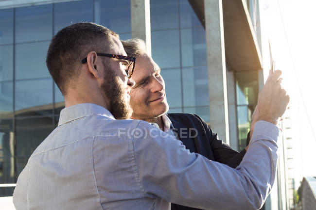 Two businessmen sharing a tablet outdoors — Stock Photo