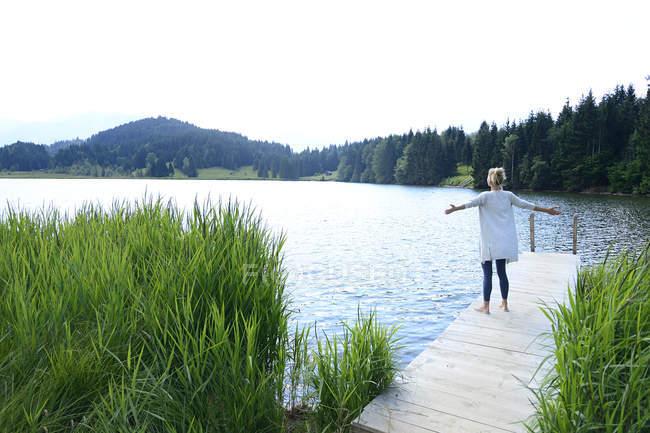Німеччина, Міттенвальд, задній погляд жінки стоячи з витягнутих рук на пристані на озері — стокове фото