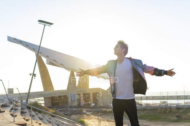 Hombre feliz de pie en la ciudad con los brazos extendidos - foto de stock