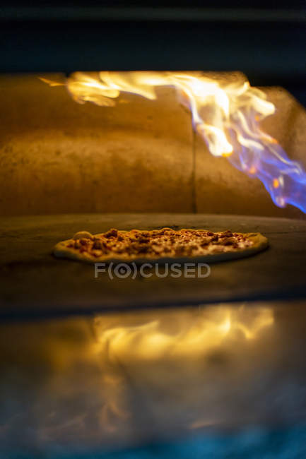 Pizza in oven with burning flame — Foto stock