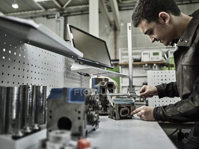 Worker in metalworking factory measuring cylinder head with caliper — стокове фото
