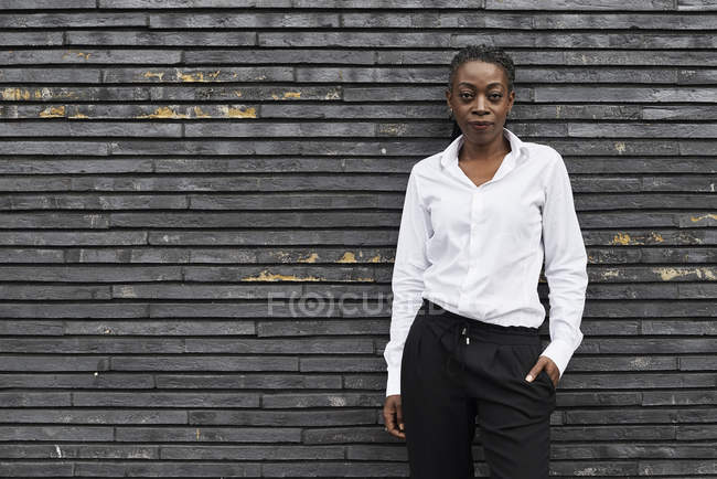 Portrait of businesswoman wearing white shirt and black trousers, leaning against wall — Stock Photo
