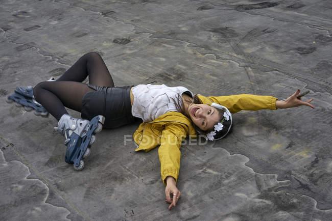 Кричущі молода жінка з вбудованими ковзанами лежачи на землі прослуховування музики з навушниками — стокове фото