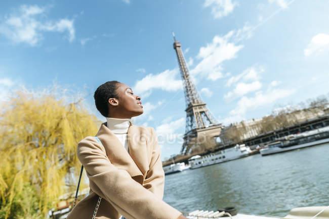 Francia, París, Mujer con los ojos cerrados en el río Sena y la Torre Eiffel en el fondo - foto de stock
