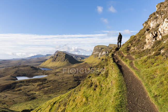 UK, Scotland, Inner Hebrides, Isle of Skye, Trotternish, hiking trail at Quiraing, Loch Cleat, hiker looking at view — Stock Photo