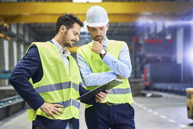 Managers wearing protective workwear looking at clipboard in factory — Stock Photo