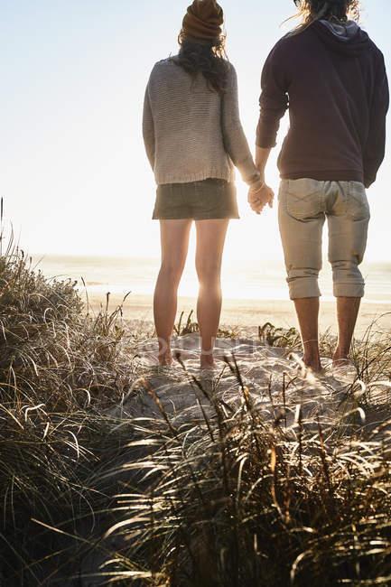 Романтична пара спостерігаючи захід сонця на пляжі — стокове фото