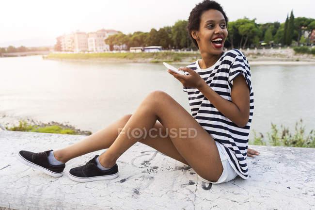 Sorrindo jovem mulher sentada na beira do rio com o uso de telefone celular — Fotografia de Stock