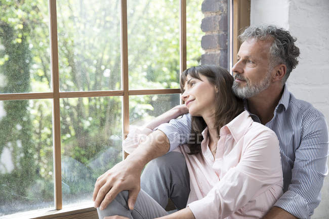 Mature couple sitting on window sill, looking out of window — Stock Photo