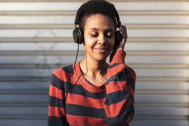 Портрет улыбающейся девушки, слушающей музыку в наушниках — стоковое фото