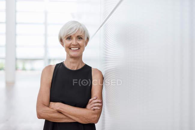Portrait de femme âgée souriante portant une robe noire appuyée contre un mur — Photo de stock