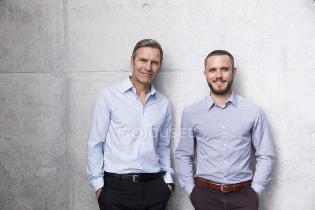 Portrait of two smiling businessmen posing at wall — Stock Photo