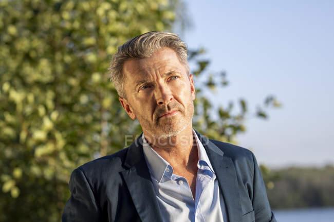 Retrato de homem de negócios pensativo em pé no lago — Fotografia de Stock