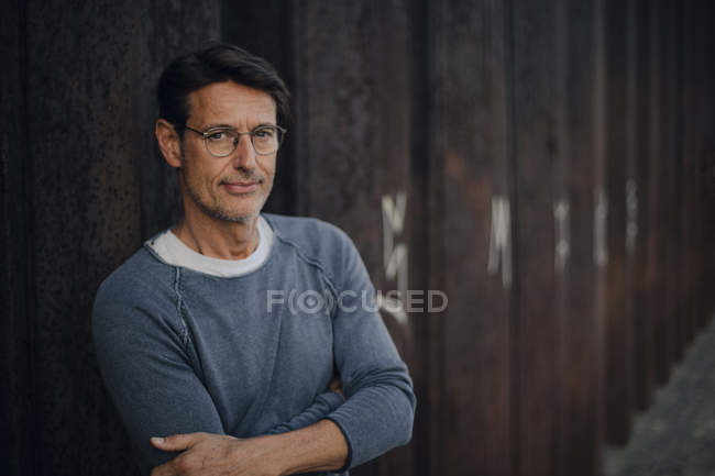 Man in front of metal wall with arms crossed, portrait — Stock Photo