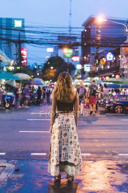 Таїланд, Бангкок, молода жінка в місті стоячи на вулиці вночі — стокове фото