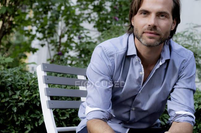 Портрет уверенного человека, сидящего на стуле в саду — стоковое фото