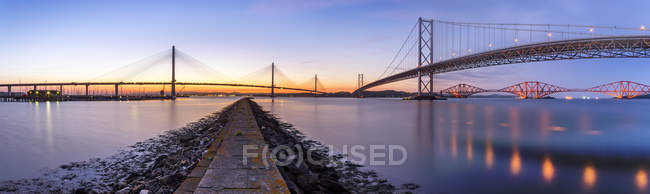 UK, Scotland, Fife, Edinburgh, Firth of Forth estuary, Panorama view from South Queensferry of Forth Bridge, Forth Road Bridge and Queensferry Crossing Bridge at sunset — Fotografia de Stock