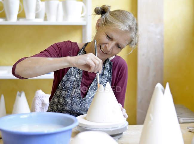 Улыбающаяся женщина работает на фарфоре в мастерской — стоковое фото
