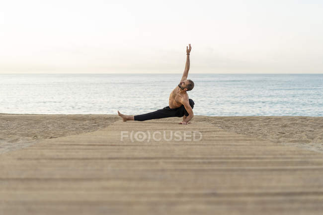 Spain. Man doing yoga on the beach in the evening — стоковое фото