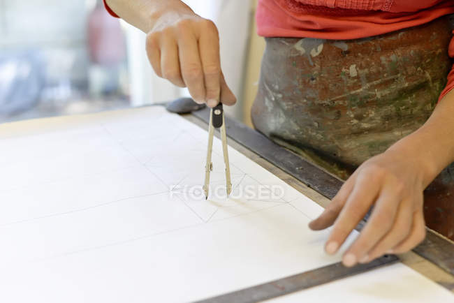 Close-up of woman working on draft in glazier's workshop — Stock Photo