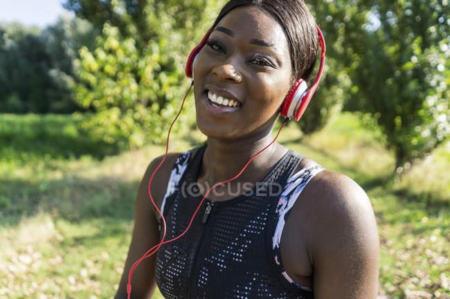 Jovem atleta na natureza, ouvindo música com fones de ouvido — Fotografia de Stock