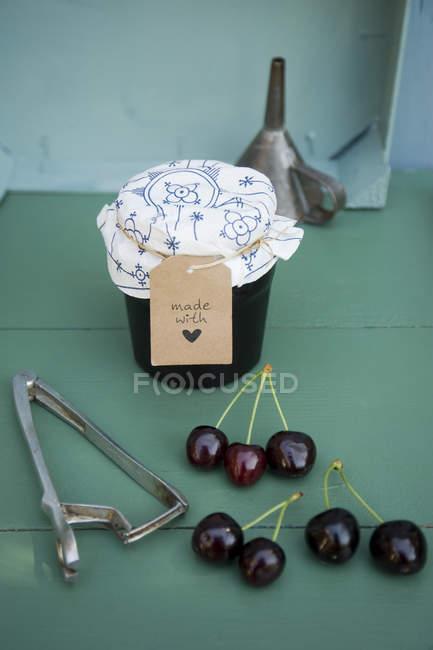 Стакан домашнего вишневого джема, вишни и вытяжки ямы — стоковое фото