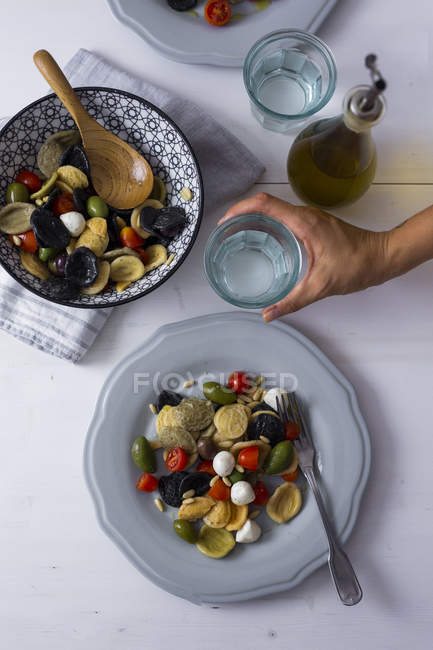 Woman serving mediterranean orecchiette with tomatoes, olives and mozzarella, water glass — Stock Photo