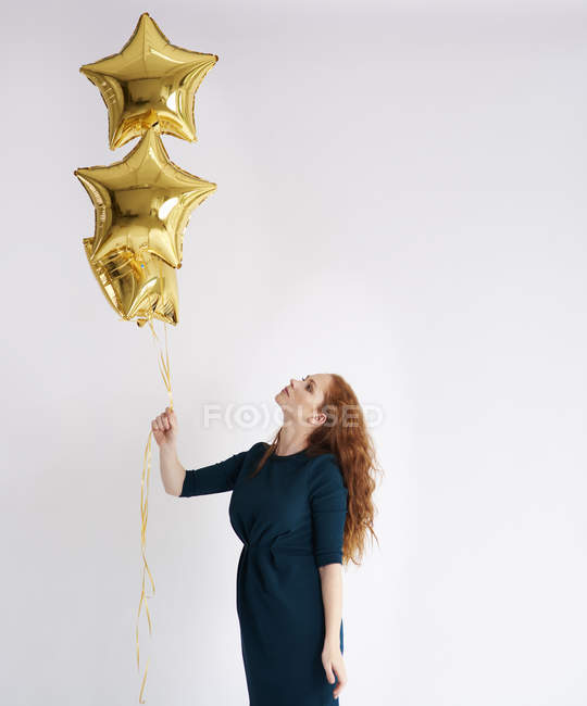 Young woman with three golden star-shaped balloons — Stock Photo