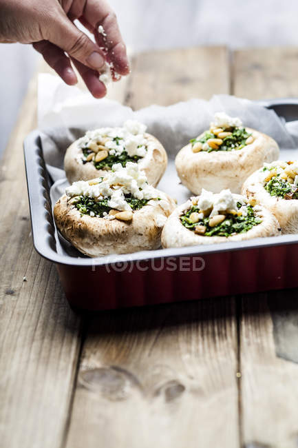 Woman Filled champignons with spinach and feta in gratin dish — Foto stock