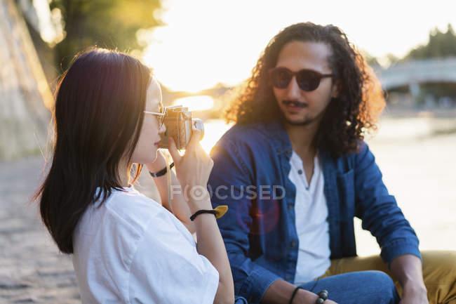 Франція, Париж, молода жінка з хлопцем, беручи фотографії на річці Сени на заході сонця — стокове фото