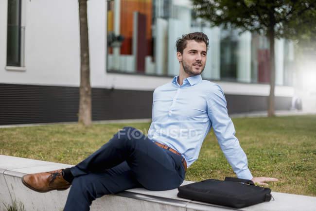 Smiling businessman sitting outdoors looking sideways — Stock Photo