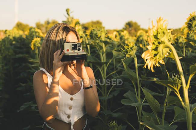 Молода жінка в області Соняшники зйомки з миттєвою камерою — стокове фото