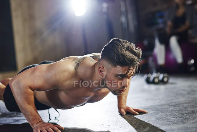 Uomo serio facendo push up in palestra — Foto stock