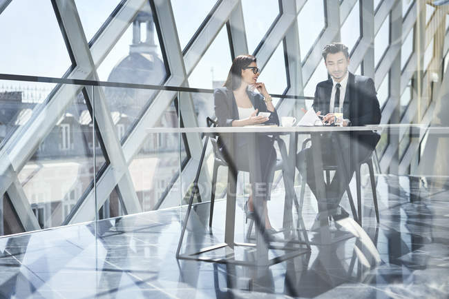 Imprenditrice e uomo d'affari che parlano alla scrivania in un ufficio moderno — Foto stock