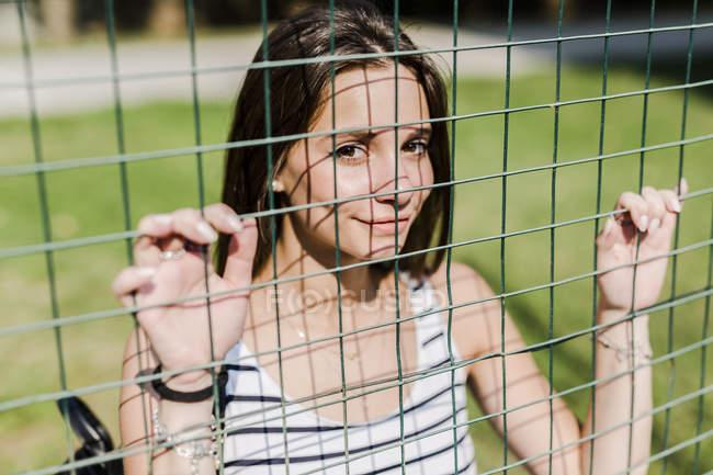Портрет улыбающейся молодой женщины за забором — стоковое фото