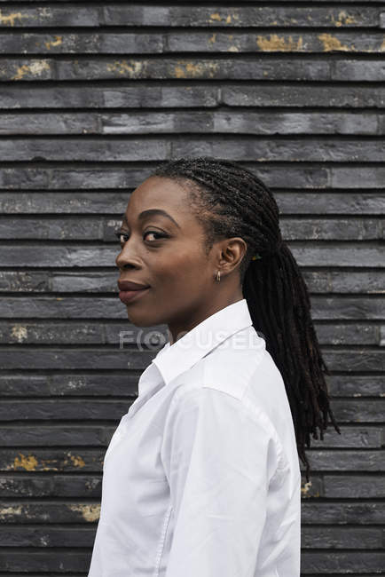 Portrait of smiling businesswoman with dreadlocks wearing white shirt — Stock Photo