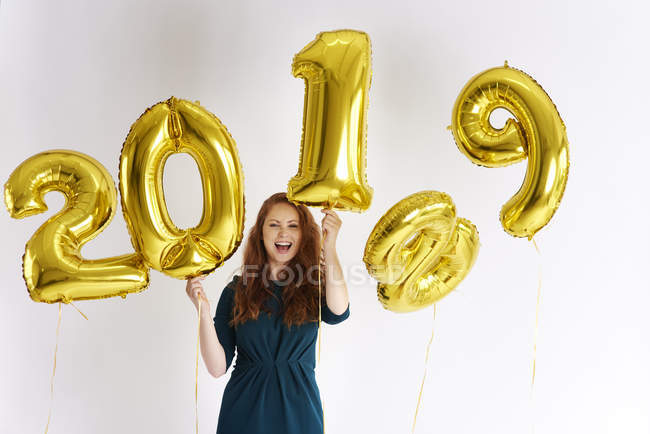 Portrait of happy young woman with golden balloons forming date 2019 — Stock Photo