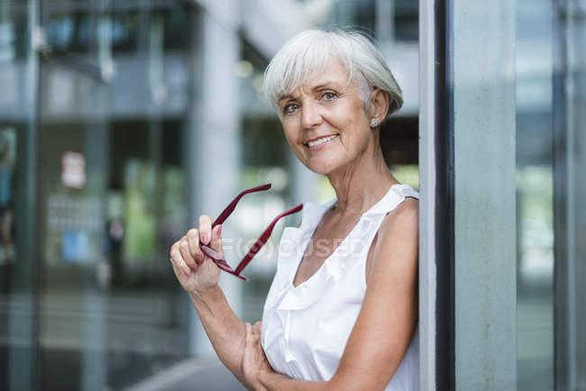 Portrait de femme âgée souriante tenant des lunettes devant une façade en verre — Photo de stock