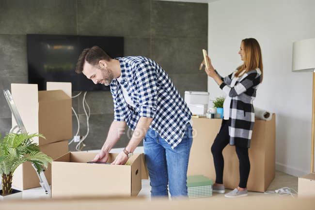 Пара переезжает в новую квартиру, распаковывает картонную коробку. — стоковое фото