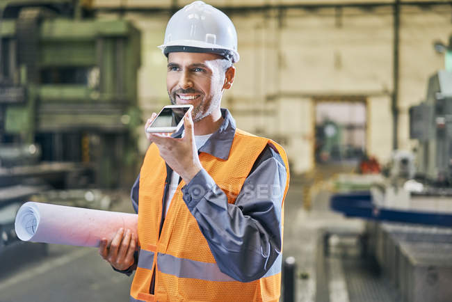 Smiling man holding blueprint and using cell phone in factory — Stock Photo