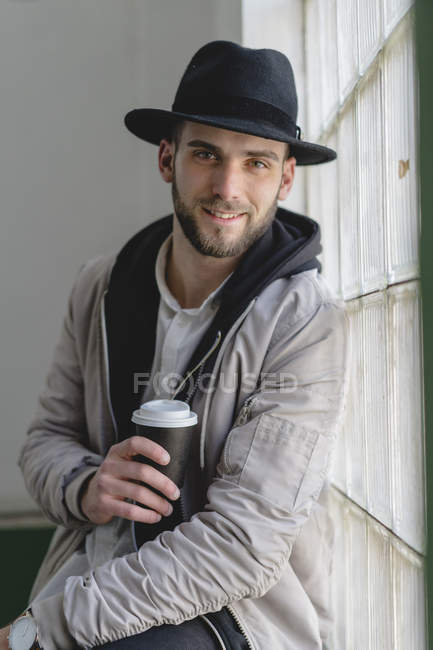 Smiling bearded man wearing black hat, holding coffee to go — Stock Photo