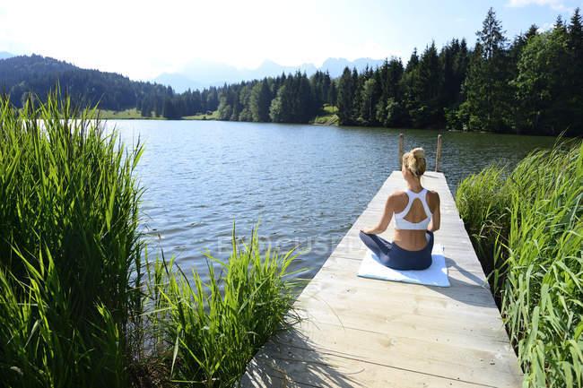 Німеччина, Mittenwald, задній погляд жінки практикуючих йогу на пристані в озері — стокове фото